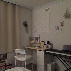 """책상과 서랍장, 피아노가 있는 부분은 이렇게 꾸몄어요. 2018년 포스터 달력을 크게 붙여놓고, 그림 몇 장과 드라이 플라워 ,네트 백 등이 있고, 책상에는 드라이 플라워, 포스터 액자, 시계, 공부하는 데에 필요한 여러 가지 학용품과 물건들이 있습니다. 외에도 많은 물건이 서랍장에 담겨있어요.  커튼은 아이보리 색상의 암막커튼을 선택했어요. 커튼 바로 옆에 네트 백과 그 안에 프리저브드 플라워를 담아서 꾸몄는데요, 제가 제일 좋아하고 자주 가는 카페에서 구매했어요. 너무 예쁘고 마음에 쏙 들어서 보자마자 카페 사장님께 """"우와, 이거 뭐에요?! 우와! 이거 살게요!!"""" 이러면서 즐거웠던 기억이 있네요."""